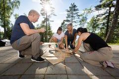 Mitarbeiter, die hölzernes Planken-Puzzlespiel auf Patio lösen stockbild