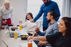 Mitarbeiter, die im Büro besprechen und zu Mittag essen lizenzfreies stockbild