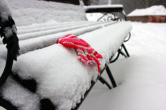 Mitenes/luvas pequenos do bebê que penduram por uma linha no dia de inverno sob a neve de queda Imagem de Stock Royalty Free