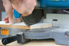 Miter Saw. Shown while cutting trim with dust blowing down from the blade housing royalty free stock photography