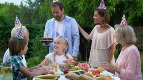 Mitfühlende Eltern, die Kuchen mit den Kerzen, Geburtstag der Tochter feiernd holen stock video