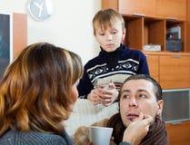 Mitfühlende Familie, die dem unwohlen Mann Medikament gibt Stockfotos
