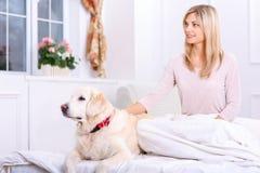 Mitfühlende Frau, die auf Bett mit ihrem Hund liegt Lizenzfreie Stockfotos