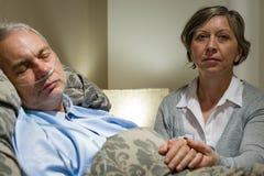 Mitfühlende Frau, welche die Hände des kranken älteren Ehemanns hält Stockfotografie