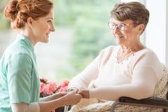 Mitfühlende Krankenschwester, die einen geriatrischen behinderten Patienten w erklärt stockfotografie