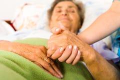 Mitfühlende Krankenschwester Holding Hands Lizenzfreies Stockfoto
