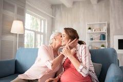Mitfühlende liebevolle Mutter, die warm sich fühlt, ihre vorwegnehmende Tochter küssend stockbild