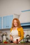 Mitfühlende mittlere Greisin, die Abendessen für ihre Familie kocht Stockfoto