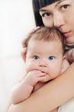 Mitfühlende Mutter, die ihr kleines nettes Baby, Familienkonzept küsst Stockfotografie