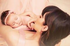 Mitfühlende Mutter, die mit Liebe ihren kleinen netten Schlafenbaby Gi hält Lizenzfreie Stockfotografie