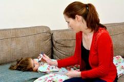 Mitfühlende Mutter, die um ihrem kranken Mädchenkind sich kümmert Stockfotografie
