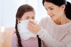 Mitfühlende nette Mutter, die ihrer kranken Tochter hilft lizenzfreies stockfoto