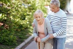 Mitfühlender älterer Ehemann, welche kranker Frau im Park hilft Stockbild