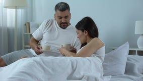 Mitfühlender Ehemann, der geliebter Frau, Flitterwochen wohlriechenden frischen Kaffee im Bett holt stock footage