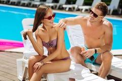 Mitfühlender Freund, der Sonnenschutzcreme auf Haut der Freundin setzt Stockbild