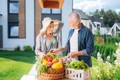 Mitfühlender liebevoller Ehemann, der seinem Fraustehenden äußeren und kochenden Salat hilft stockfotografie