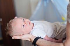 Mitfühlender Vater, der neugeborenen netten Sohn in seinen Armen hält Lizenzfreie Stockbilder