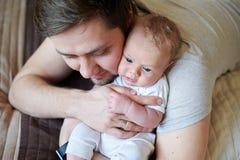 Mitfühlender Vater, der neugeborenen netten Sohn in seinen Armen hält Lizenzfreies Stockfoto