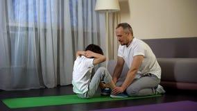 Mitfühlender Vater, der seine Sohnbeine beim Handeln von Krisen, Sportlebensstil hält lizenzfreies stockbild