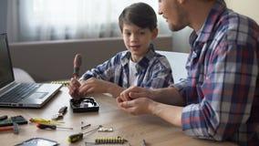Mitfühlender Vater, der seinen kleinen Sohn unterrichtet, Festplattenlaufwerk zu Hause zu reparieren, Hobby stock footage