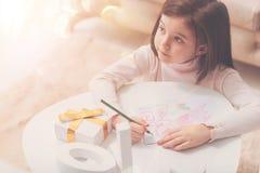 Mitfühlendes künstlerisches Mädchen, das ein Bild für ihre Mutter macht Lizenzfreie Stockbilder