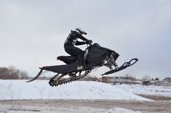 Mitfahrer auf dem Snowmobilespringen Lizenzfreies Stockfoto