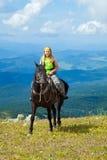 Mitfahrer auf Pferderuecken an den Bergen Stockfotografie