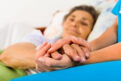 Mitfühlende Krankenschwester Holding Hands Lizenzfreie Stockfotos