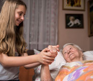 Mitfühlendes Mädchen, das altes lady& x27 hält; s-Hände Stockfotos