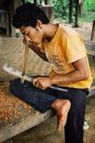Mitglied des lokalen Drachebootsteams, das für den Wettbewerb durch das Schnitzen seines eigenen Paddels sich vorbereitet stockbild