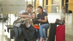 Mitglieder einer großen Familie passen Fotos von den Ferien im Tablet-PC beim Sitzen im Warteraum des Flughafens auf oder stock footage
