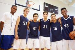 Mitglieder männlichen Highschool Basketballs Team With Coach Lizenzfreie Stockbilder