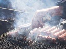 Mititei rumano y cocinado en la parrilla en el humo imagenes de archivo