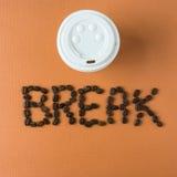Mitnehmerkaffeetasse mit Wort BRUCH buchstabierte in den Bohnen Stockfotografie