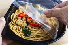 Mitnehmerlebensmittelfertiggericht: Die Frauenhände halten offen haften Verpackung a an lizenzfreie stockfotografie