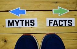 Mitos o hechos enfrente de señales de dirección con las zapatillas de deporte en de madera imagen de archivo