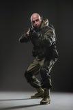 Mitragliatrice della tenuta dell'uomo del soldato su un fondo scuro Fotografia Stock Libera da Diritti