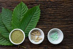 Mitragyna speciosa kratom leaves with medicine products in powder, capsules and tablet in white ceramic bowl with wooden texture. On background Stock Photo