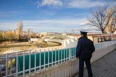 MITROVICA, IL KOSOVO - 11 NOVEMBRE 2016: Poliziotto del Kosovo che guarda il ponte sul fiume di Ibar immagini stock