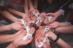 Mitschüler halten Hände zusammen mit Glocken letzter Tag in der Schule Lizenzfreie Stockfotos