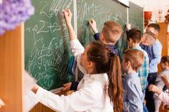 Mitschüler zeichnen auf ein Brett während des Bruches stockbild