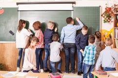 Mitschüler zeichnen auf ein Brett während des Bruches lizenzfreie stockfotos