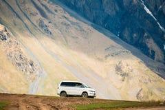 Mitsubishi Delica przestrzeni przekładni jeżdżenie z na drodze na lato góry tle Obrazy Royalty Free