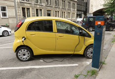 Mitsubishi electric car recharging. COPENHAGEN, DENMARK - CIRCA JUNE 2016: yellow Mitsubishi electric car recharging on the street Stock Photos