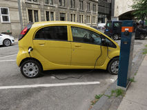 Mitsubishi electric car recharging. COPENHAGEN, DENMARK - CIRCA JUNE 2016: yellow Mitsubishi electric car recharging on the street Royalty Free Stock Photography