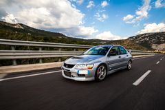 Mitsubishi EVO 8 on highway. Trieste, Italy - SEPTEMBER 3, 2013: Photo of Mitsubishi EVO 8 .The Lancer Evolution 8 sedan features a newly designed 4B11T 2.0L royalty free stock image