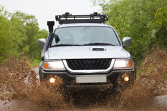 Mitsubishi Pajero moving by water making lots of splashes Stock Photo