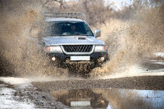 Mitsubishi Pajero Sport on dirt road in early spring making spla royalty free stock photo