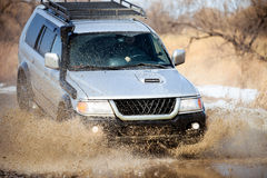 Mitsubishi Pajero Sport on dirt road in early spring making spla Royalty Free Stock Image