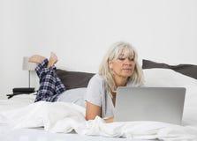 Mitt- ålderkvinna med en bärbar dator i säng Arkivbilder